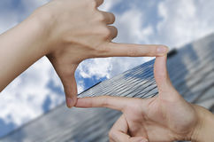 Vision of a glass business building. Out of focus business building and fingers creating a square making the vision clear Royalty Free Stock Photo