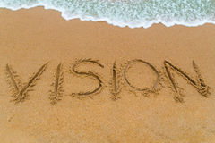 VISION inscription written on sandy beach with wave approaching Royalty Free Stock Image