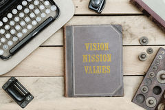 Vision, Mission, Values on old book cover at office desk with vi Royalty Free Stock Photography