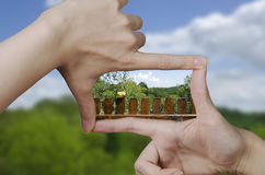 Vision of a picket fence with apple. Out of focus empty nature landscape and fingers creating a square making the vision of the future clear Royalty Free Stock Image