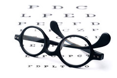 Vision screening. Old-fashioned round black eyeglasses, lying over the eye-checking chart Stock Photography