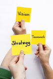 Vision Teamwork Strategy. Group of people holding adhesive notes with 'Vision' , 'Teamwork' and 'Strategy' words Royalty Free Stock Photography