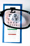 Vision test with eye. This stock photo shows a vision test through glasses, from the patient perspective.  The patients eye is seen reflected in the glasses Stock Photos