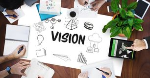 Vision text by icons and business people on table. Digital composite of Vision text by icons and business people on table Royalty Free Stock Photography
