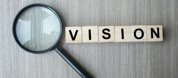 Vision text wooden cubes and magnifying glass on wood table background. SEO, Idea, Strategy, Analysis, goals and Values concept. Vision text wooden cubes and stock image