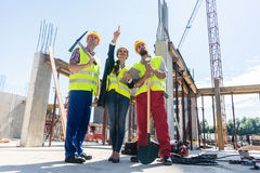Visionary architect pointing up while guiding and motivating wor. Low-angle view of a visionary architect pointing up while guiding and motivating two workers on Royalty Free Stock Photos
