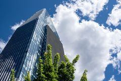 Visionary skyscraper surrounded by clouds. Visionary and futuristic skyscraper with sky reflected on windows, modern shape skyscraper with cloudy sky background royalty free stock image