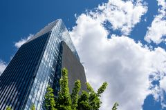Visionary skyscraper surrounded by clouds. Visionary and futuristic skyscraper with sky reflected on windows, modern shape skyscraper with cloudy sky background stock photo