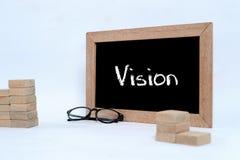Visione sulla lavagna con scrittura del gesso Blocchetto legno di vetro dell'occhio e che impila come simbolo della scala di punt fotografia stock