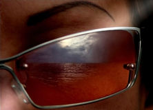Visions of life. Reflection of the sea and clouds in glasses Royalty Free Stock Photos