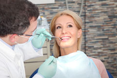 Visit at the dentist. Close-up portrait of an attractive women sitting at dentist office while male dentist checking her teeth royalty free stock image