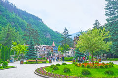 Visit mineral water resort. BORJOMI, GEORGIA - MAY 26, 2016: The central alley of Mineral Water Park with beautiful flower bed, surrounded by benches, on May 26 Royalty Free Stock Photos