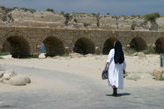 Visit to the holy land. A nun at the aqueduct, Caesarea, Israel stock images