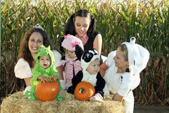 Visit to a Pumpkin Patch. Three women and three toddlers in Halloween costumes visit a pumpkin patch. They are sitting on a hay bale Royalty Free Stock Photo