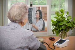 Visit to virtual doctor via computer. Old retired women sitting in front of computer monitor. She has just sent her blood pressure and pulse information to Stock Images