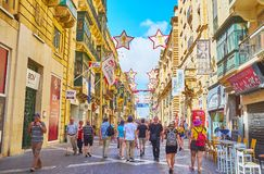 Visit Valletta old town, Malta. VALLETTA, MALTA - JUNE 17, 2018: The medieval Republic street with scenic stone edifices is decorated due to the Film Festival Stock Image