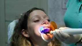 Visita al dentista, installazione del sistema del sostegno L'assistente splende con un ultravioletto dentario di polimerizzazione video d archivio
