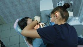 A visita ao doutor de Orthodontist do dentista ajusta-se - acima das cintas do ferro para uma mulher com um fixator dental, vista vídeos de arquivo