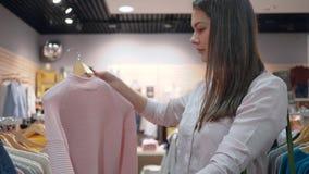 A visita da loja, mulher shopaholic bonita escolhe a roupa nova na loja da forma durante descontos na alameda vídeos de arquivo