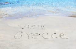 Visita Grecia escrita en la arena imágenes de archivo libres de regalías