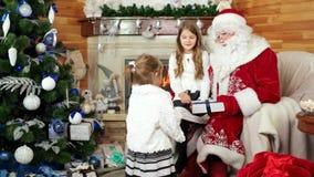 Visita santa en su residencia, hermana feliz de las niñas que se sienta en el revestimiento de Papá Noel, regalos de la Navidad almacen de video