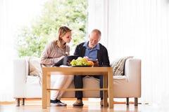 Visitante da saúde e um homem superior com a tabuleta durante a visita home fotografia de stock royalty free