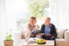 Visitante da saúde e um homem superior com a tabuleta durante a visita home fotografia de stock