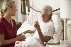 Visitante da saúde que dá a medicamentação masculina superior na cama em casa fotos de stock