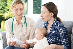 Visitante da saúde que dá o conselho da mãe no bebê de alimentação com garrafa Fotografia de Stock