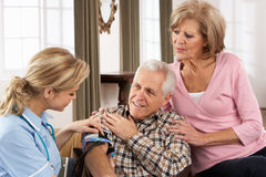Visitante da saúde que toma a pressão sanguínea de homem sênior Foto de Stock