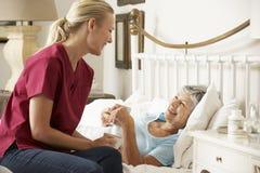 Visitante da saúde que fala ao paciente superior da mulher na cama em casa Fotografia de Stock