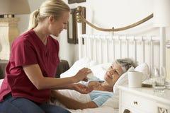 Visitante de la salud que da la medicación mayor de la mujer en cama en casa Foto de archivo