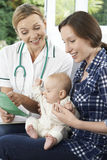 Visitante de la salud que discute el prospecto con la madre que celebra al bebé en Ho Fotos de archivo libres de regalías