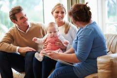 Visitante de la salud que habla con la familia con el bebé joven fotos de archivo libres de regalías
