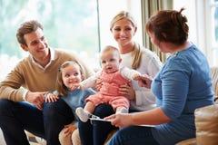 Visitante de la salud que habla con la familia con el bebé joven Imágenes de archivo libres de regalías