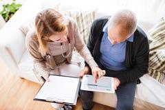 Visitante de la salud y un hombre mayor con la tableta durante la visita casera imagenes de archivo