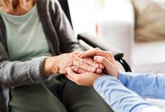 Visitante irreconocible de la salud y una mujer mayor durante la fuerza casera imágenes de archivo libres de regalías