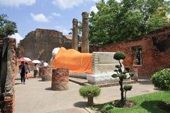 Visitante que ruega al Buda durmiente en el templo antiguo, en Ayutthaya, Tailandia Fotografía de archivo libre de regalías