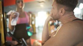 Visitante regular que flerta com um instrutor fêmea novo da aptidão, uma comunicação do gym vídeos de arquivo