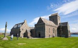 Visitantes británicos de Iona Abbey Scotland que disfrutan del tiempo hermoso en este hito histórico en la isla escocesa Foto de archivo