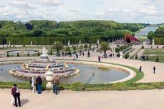 Visitantes en el palacio Versalles del jardín con la estatua y la charca en París, Francia Foto de archivo libre de regalías