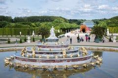 Visitantes en el palacio Versalles del jardín con la estatua y la charca en París, Francia Foto de archivo