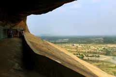 Visitantes en las camas de piedra jain del complejo sittanavasal del templo de la cueva Imagen de archivo