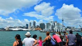 Visitantes en un barco de la travesía que mira horizonte de la costa de Auckland Fotografía de archivo