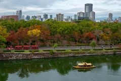 Visitantes en una tranvía y un barco de la travesía que disfrutan de colores de la estación del otoño en Osaka Castle Park en Osa foto de archivo libre de regalías