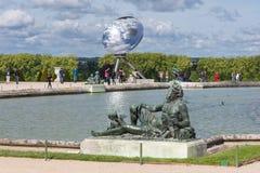 Visitantes no palácio Versalhes do jardim com estátua e na lagoa em Paris, França Imagem de Stock Royalty Free