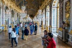 Visitantes que admiran el Pasillo del palacio Versalles de los espejos cerca de París, Francia Imagen de archivo libre de regalías