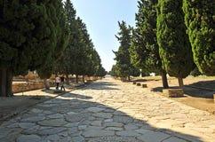 Visitantes que caminan en el Cardus Maximus, sitio arqueológico de la ciudad romana de Italica, Andalucía, España Imagen de archivo libre de regalías