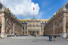 Visitantes que caminan en el palacio Versalles del patio cerca de París, Francia Fotos de archivo