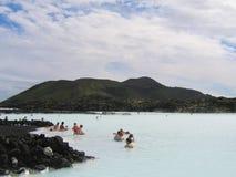 Visitantes que gozan del balneario geotérmico de la laguna azul famosa en Islandia Imágenes de archivo libres de regalías